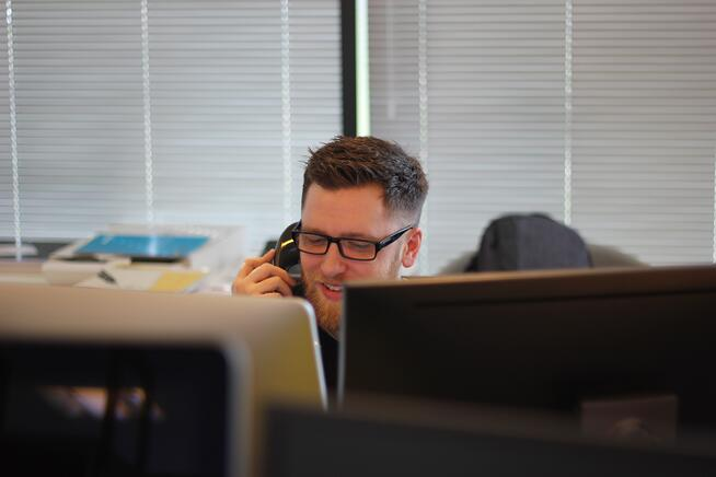 man with computers answering phone call